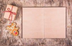 Libro aperto con le pagine vuote, il pan di zenzero e un regalo ` S del nuovo anno e Natale Ambiti di provenienza e strutture immagini stock libere da diritti