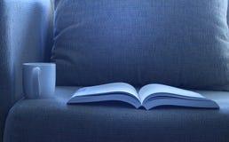 Libro aperto con una tazza del cofee sul letto Fotografie Stock