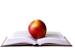Libro aperto dell'allievo con la mela rossa Fotografie Stock Libere da Diritti