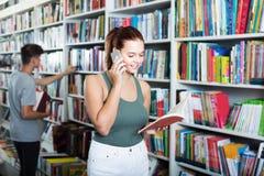 Libro aperto della tenuta della ragazza e parlare sul telefono cellulare in deposito Fotografia Stock Libera da Diritti