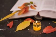 Libro aperto di poesia con la candela immagine stock