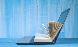 Libro aperto e computer portatile, fotografie stock