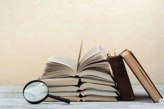 Libro aperto, libri variopinti della libro con copertina rigida sulla tavola di legno magnifier Di nuovo al banco Copi lo spazio  Fotografia Stock Libera da Diritti
