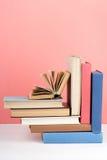 Libro aperto, libri variopinti della libro con copertina rigida sulla tavola di legno, rosso, fondo rosa Di nuovo al banco Copi l Fotografia Stock