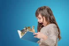 Libro aperto sorpreso della tenuta della bambina con gli animali Immagini Stock