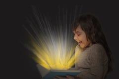 Libro aperto sorridente della tenuta della bambina con i raggi Immagini Stock