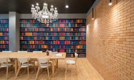 Libro aperto su una tavola di legno della piattaforma con sedie di legno e nessuno in un fondo moderno delle biblioteche immagine stock libera da diritti