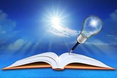 Libro aperto sul mare e cielo blu con la lampadina della matita Fotografia Stock Libera da Diritti