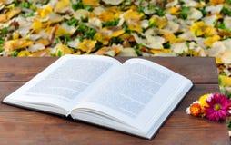 Libro aperto sulla tavola di legno con i fiori Fotografia Stock Libera da Diritti
