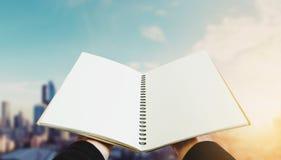 Libro aperto sulle mani con gli ambiti di provenienza della città nell'alba Immagini Stock Libere da Diritti