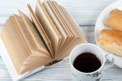 Libro aperto, tazza di caffè e spuntino sul fondo di legno della tavola Immagini Stock Libere da Diritti