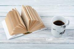 Libro aperto, tazza di caffè e spuntino sul fondo di legno della tavola Immagine Stock