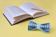 Libro aperto, una cravatta a farfalla e una matita di legno su un fondo giallo con lo spazio della copia immagine stock