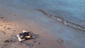 Libro ardiente en la arena en la costa metrajes