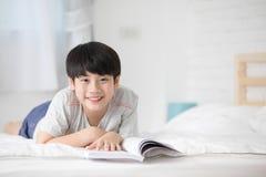 Libro asiático feliz de la historia de la lectura del muchacho en la cama imagen de archivo libre de regalías