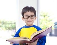Libro asiatico della holding del bambino Fotografie Stock Libere da Diritti