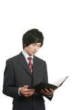 Libro asiatico della holding dell'uomo di affari Immagine Stock