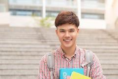 Libro asiatico della tenuta dello studente maschio dell'istituto universitario in città universitaria Fotografia Stock Libera da Diritti