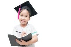 Libro asiatico felice di scrittura del laureato del bambino della scuola con il cappuccio di graduazione Immagini Stock