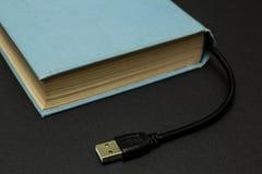 Libro azul con un conector USB en un fondo negro foto de archivo