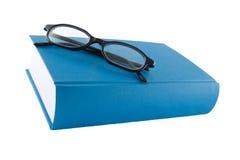 Libro azul y glasses1 negro Imagen de archivo libre de regalías