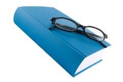 Libro azul y vidrios negros Imagen de archivo