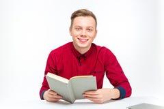 Libro bello sorridente felice di seduta e di lettura dell'uomo Fotografia Stock