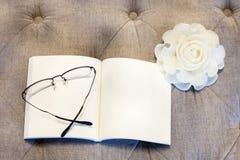 Libro in bianco con la candela rosa sul sofà con gli occhiali Immagine Stock