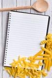 Libro in bianco di ricetta con varia pasta Immagine Stock