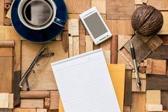 Libro Blanco con la taza y el teléfono de café en la textura de madera Fotos de archivo libres de regalías