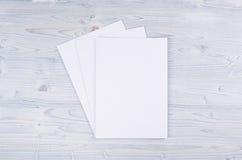 Libro Blanco en blanco A4, sobre en el tablero de madera azul claro suave Imagenes de archivo