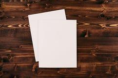 Libro Blanco en blanco A4, sobre en el tablero de madera del marrón del vintage Mofa para arriba para la identidad de marcado en  Fotos de archivo libres de regalías
