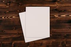 Libro Blanco en blanco A4, sobre en el tablero de madera del marrón del vintage Mofa para arriba para la identidad de marcado en  Imágenes de archivo libres de regalías