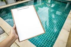 Libro Blanco en blanco en el tablero sobre fondo claro de piscina del agua Imagen de archivo libre de regalías