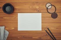 Libro Blanco en la tabla de madera con la lente de cámara foto de archivo libre de regalías
