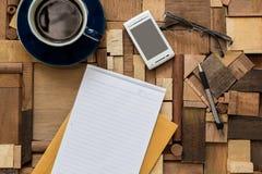 Libro Blanco y café ascendentes y teléfono en la textura de madera Fotografía de archivo libre de regalías