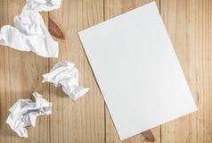 Libro Blanco y documento arrugado sobre fondo de madera Imágenes de archivo libres de regalías