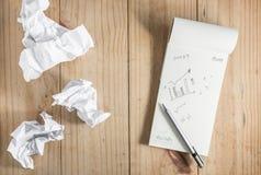 Libro Blanco y lápiz de papel y gris arrugado en backgro de madera Imagen de archivo libre de regalías