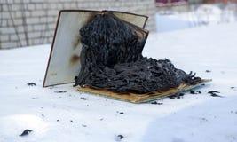 Libro bruciante in neve pagine con il testo nell'ustione del libro aperto con la fiamma luminosa fotografie stock