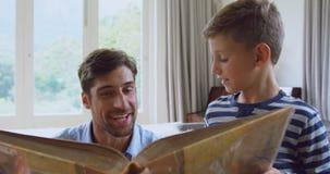 Libro a casa 4k di storia della lettura del figlio e del padre archivi video