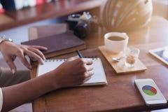 Libro casual de la escritura del hombre de negocios con un teléfono y una cámara en el th Imágenes de archivo libres de regalías