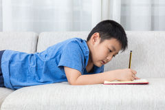 Libro cinese asiatico di scrittura del ragazzino sul sofà fotografia stock