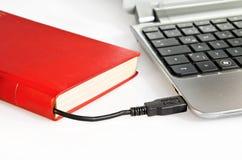 Libro collegato ad un computer via il cavo di USB fotografia stock