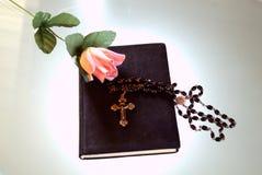 Libro con color de rosa y crucifijo Imagen de archivo