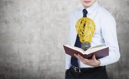 Libro con el bulbo amarillo Imágenes de archivo libres de regalías