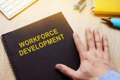 Libro con el desarrollo de la mano de obra del título en el escritorio imagen de archivo