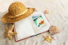 Libro con el sombrero de paja y seashells en arena Imagenes de archivo