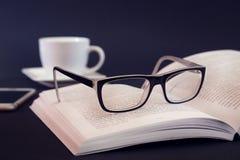 Libro con el vidrio en la tabla Fotografía de archivo libre de regalías