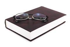 Libro con gli occhiali su bianco Immagine Stock