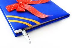 Libro con il nastro e la penna Immagini Stock